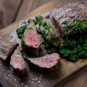 Medium rare grilled beef steak with chimmichurri sauce, close-up